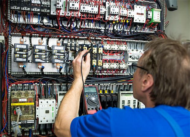 Mitarbeiter beim Überprüfen einer Elektroinstallation
